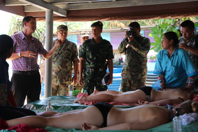 Astonished tourists watch as armed police and marines visit Phuket beach