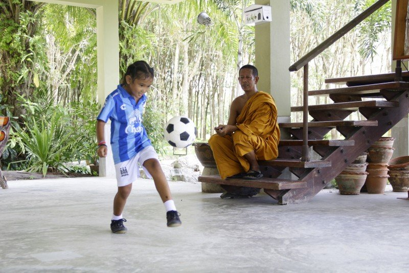 Jao Pok – the football monk in Phang Nga with his pupil, 7-year-old Tang Mo practicing her juggling skills. Photo: Steven Layne