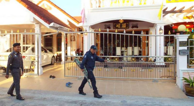 An officer exits the home of Srisoonthorn Mayor Worawut Songyos while carrying a firearm found inside the house. Photo: Eakkapop Thongtub