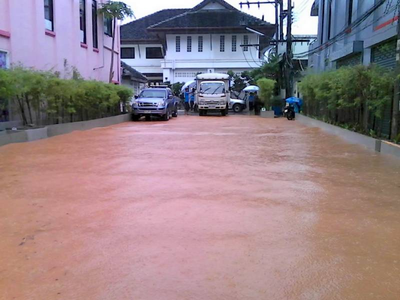 Home owners in Patong wait for floodwaters to subside after heavy rain this morning (July 19). Photo: Kathu Civil Defense Volunteers