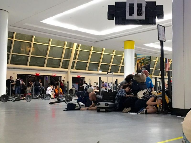 Passengers take shelter at immigration control after false reports of a shooting set off a security alert at JFK International airport in New York on Sunday (Aug 14). Photo: Photo: AFP / Brigitte Dusseau