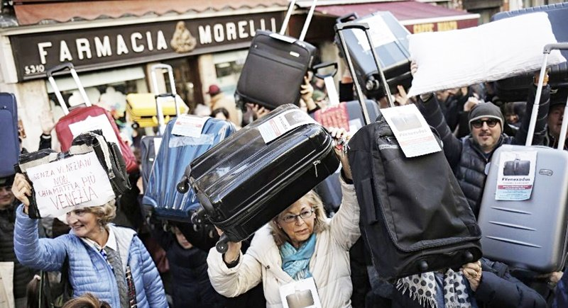 People hold suitcases and signs as they demonstrate against the increasing number of tourists in Venice. Photo: Marco Bertorello/AFP
