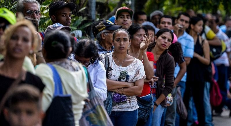 People queue to buy basic food and household items outside a supermarket in Caracas. Photo: Federico Parra/AFP