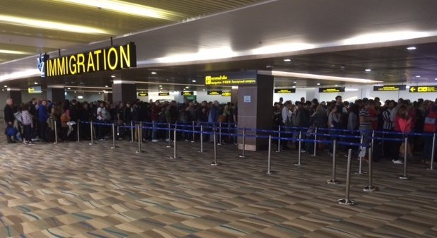 The Arrivals Hall at Phuket International Airport is crammed as tourists wait hours to clear immigration.