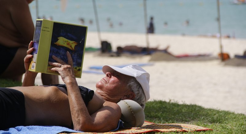 A man relaxes reading a book at a beach in Phuket. Photo: Tanyaluk Sakoot