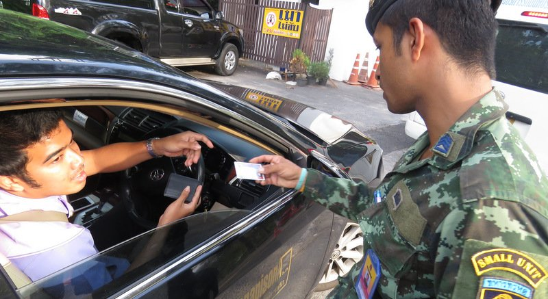 A soldier checks a hotel driver's licence at a checkpoint in Kamala. Photo: PLTO