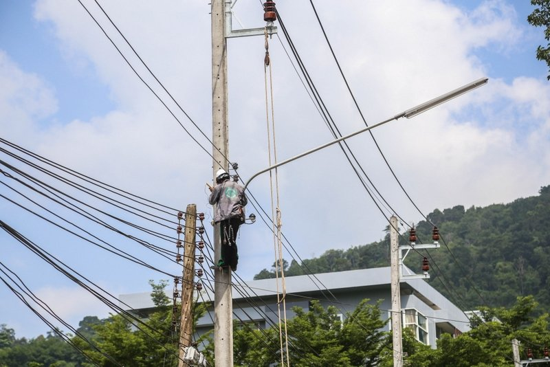 A worker tidies up cables strung up to a power pole. The mess of communications cables hanging along the streets throughout the country have become a national eyesore. Photo: Patong Municipality