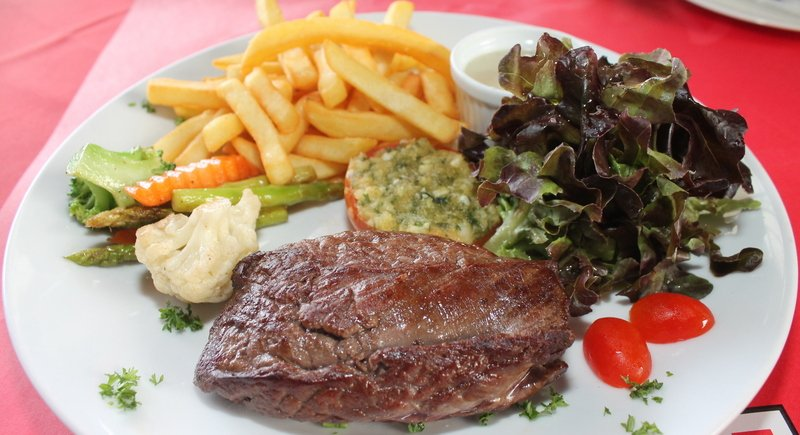 Steak La Boucherie with French fries, salad, seasonal vegetables, stuffed tomato and blue cheese sauce.