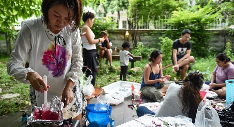 Prontip Mankong, a former political prisoner, melting lipstick as fellow ex-inmates and volunteers help recycle cosmetics in Bangkok. Photo: Lillian Suwanrumpha/AFP