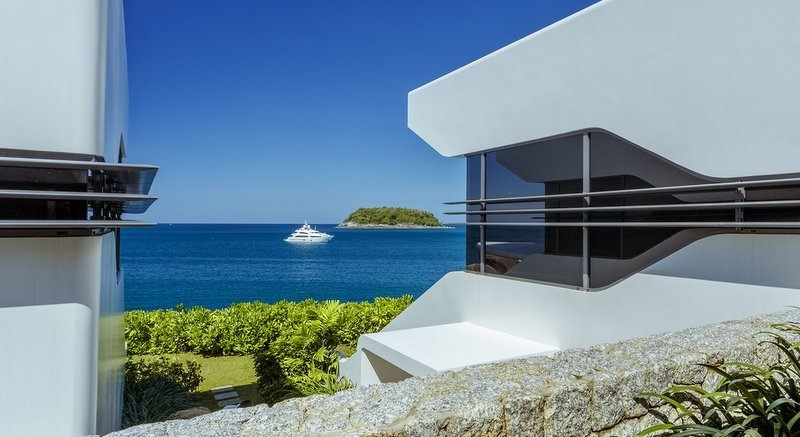A superyacht can be seen moored in Kata bay from between two of  Kata Rocks' luxury villas.