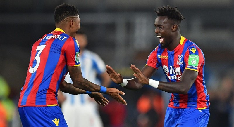 Crystal Palace's Pape Souare (right) gestures to Patrick van Aanholt as he starts the second half after missing most of last season. Photo: Glyn Kirk / AFP