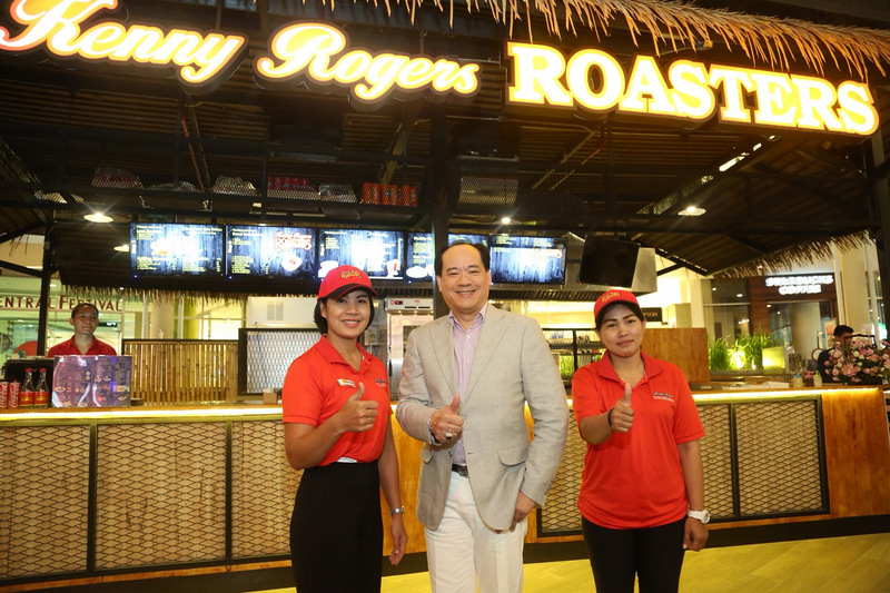 Central Pattana Plc (CPN) Chief Operating Officer Pakorn Partanapat (centre) gives the thumbs-up for Public House in front of Kenny Rogers Roasters. Photo: CPN