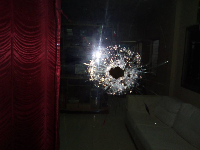 Bullet holes were found on a Yamaha motorbike, a wall and a window pane. Photo: Eakkapop Thongtub