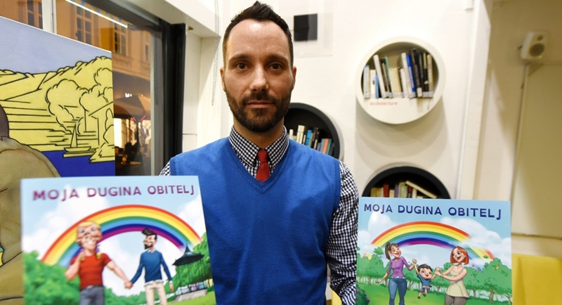 Ivo Segota, co-author of the book 'My Rainbow Family', the country's first picture book for children about 'rainbow families', holds copies of the book in his hands after its presentation in Zagreb. Photo: AFP