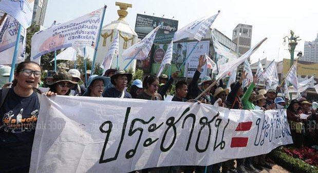 Members of the People Go Network hold up banners calling for democracy after arriving at the Democracy Monument in Muang district in Khon Kaen province on Friday. Photo: Patipat Janthong