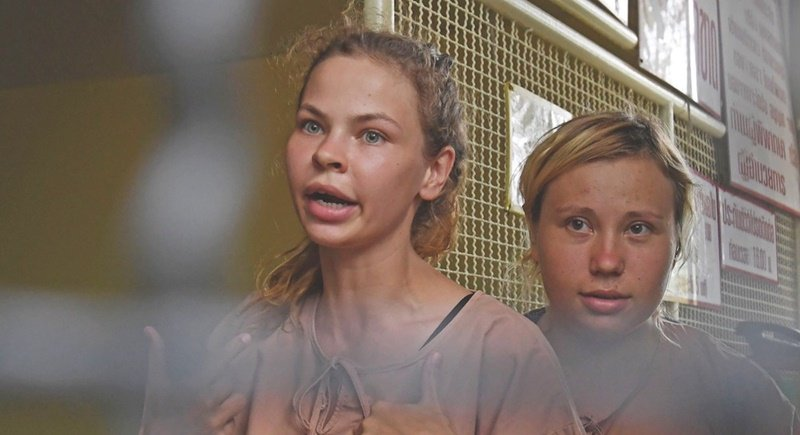Detained Belarusian model Anastasia Vashukevich (left) arrives with an unidentified fellow detainee at a holding cell to face trial at a court in Pattaya yesterday (Apr 17), following a police raid on a sex training course. Photo: AFP