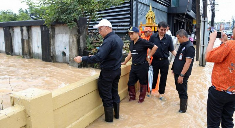 Phuket Governor Norraphat Plodthong (2nd from left) stands on a bridge in Phuket Town last September as surging floodwaters place unprecedented pressure on the bridge's structural supports. Photo: PR Dept / file