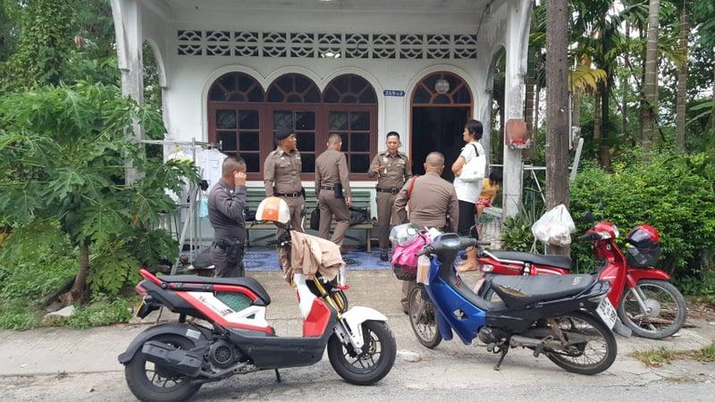 POlice wait outside the house looking for Mr Thitisan. Photo: Eakkapop Thongtub