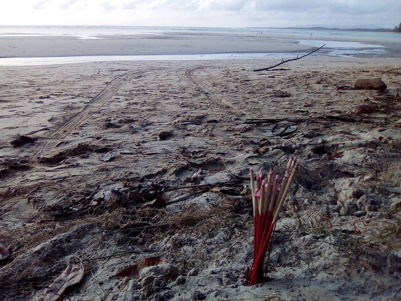 Incense sticks have been placed in the sand at Nai Yang Beach amid prayers for young Supat. Photo: Eakkapop Thongtub