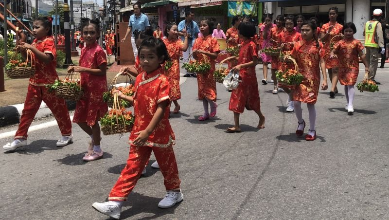 The Procession including school children bring their gifts to the ghosts through Phuket Town
