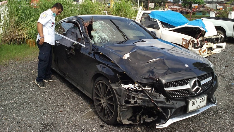 A rescue worker inspects the damaged Phuket-registered Mercedes-Benz C250. Photo: Eakkapop Thongtub
