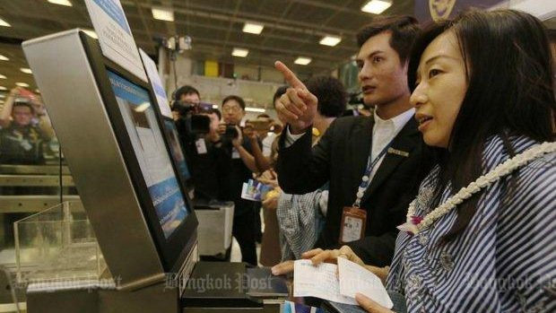 A Chinese tourist gets some help with an e-immigration display at Suvarnabhumi airport. A new series of tourism stimulus measures include visa-fee waivers for some. Photo: Post Today / Amornthep Chotchalermpong