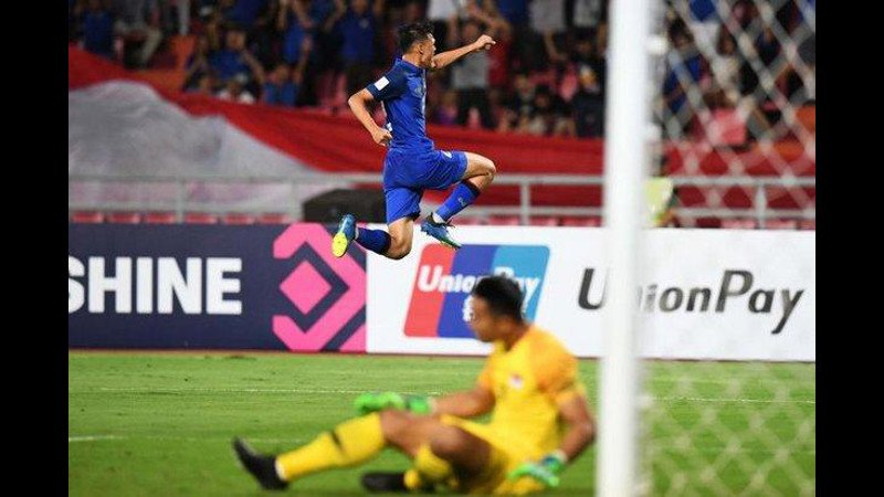 Thailand's forward Supachai Jaided celebrates with a leap over Singapore goalkeeper Hassan Sunny after scoring the second goal of the match in the 23rd minute. Photo: AFP