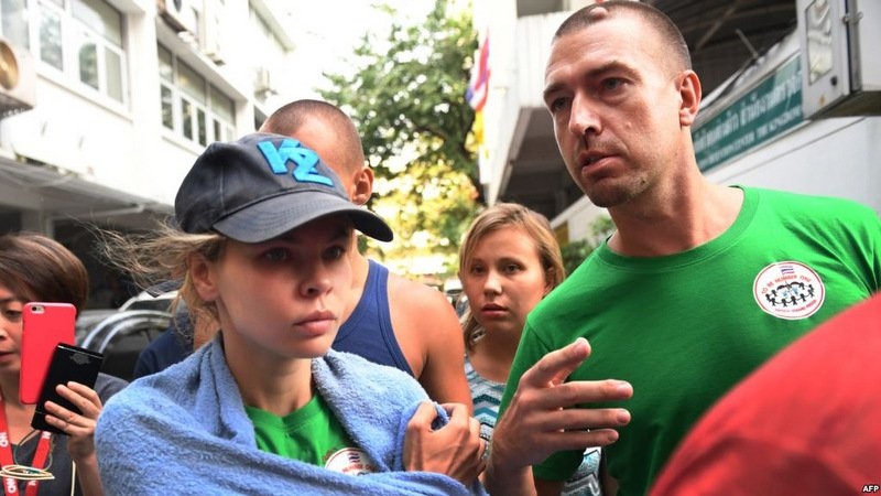 Detained Belarusian model Anastasia Vashukevich, (L) known by her pen name Nastya Rybka with Russian seduction guru Alex Kirillov (R) leave Thai immigration department in Bangkok on Thursday (Jan 17). Photo: Lillian Suwanrumpha / AFP
