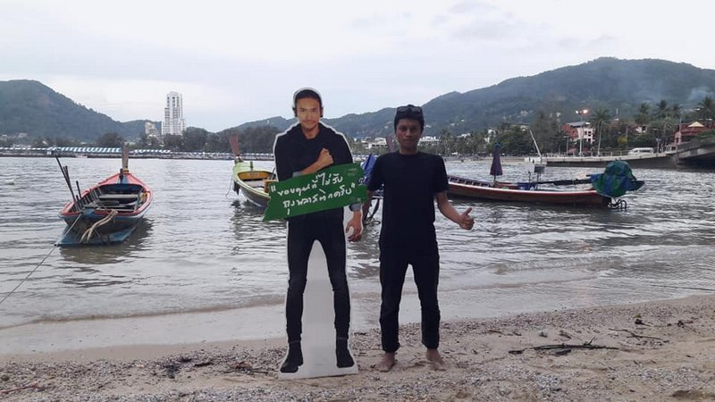 """Patong council worker Theeraphong Penmit (right) poses with a poster stand of one of his heroes,  Artiwara """"Toon Bodyslam"""" Khongmalai. Photo: Theeraphong Penmit"""