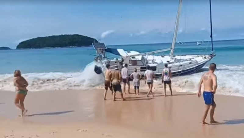 Phuket tourists lend a hand recovering beached yacht at Nai Harn
