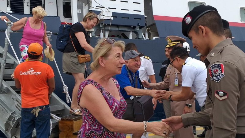 Tourists alight from Belgium-flagged cruiser 'La Belle Des Ocean' and thank officers after their ship hit the rocks near Pida islet. They were safely taken to a Phuket port. Photo: Bangkok Post