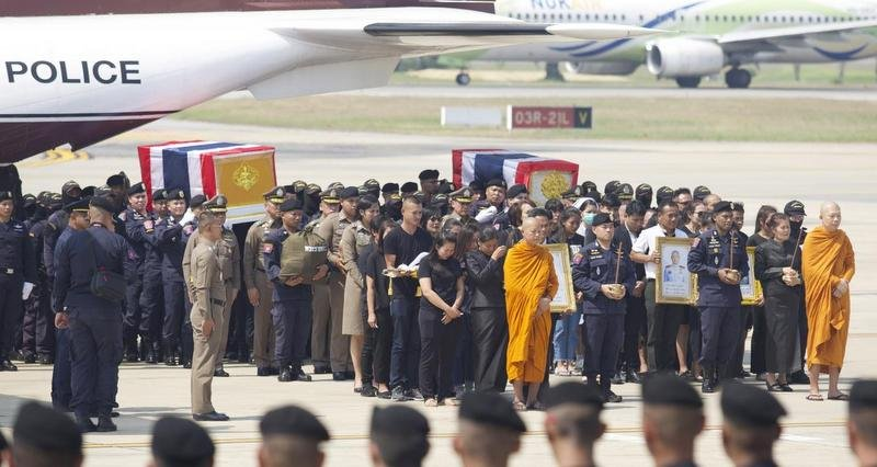 The national flag-covered coffins of Pol Capt Trakul Tha-asa and Pol Snr Sgt Maj Petcharat Kamchadpai are carried from Wing 6 at Bangkok's Don Muang air base to Wat Tri Thotsathep in Phra Nakhon district for royally sponsored bathing rites. Photo: Apichit Jinakul