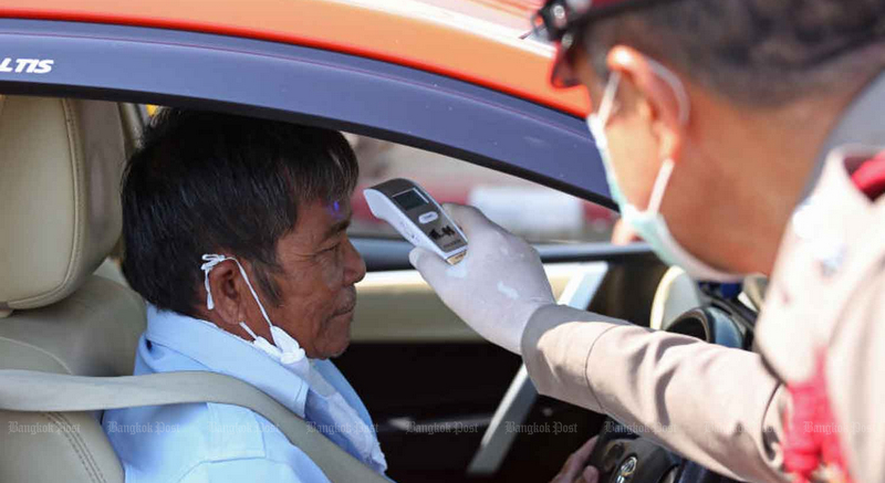 A policeman checks a taxi driver's body temperature on Suwinthawong Road in Bangkok today (Mar 26), as the number of local cases of COVID-19 exceeded 1,000. Photo: Varuth Hirunyatheb