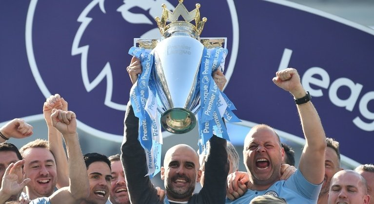 Manchester City manager Pep Guardiola holds up the Premier League trophy. Photo: AFP