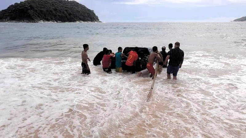 Lifeguards and officers from Rawai Municipality took 30 minutes to pull the pickup truck back onto the beach. Photo: Witanya Chuayuan