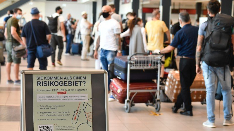 People queue near an information board promoting free COVID-19 tests for travellers arriving at Berlin-Schoenefeld airport in Schoenefeld, south of Berlin, on July 31, 2020. Germany made coronavirus tests mandatory for travellers returning from at-risk areas, as fears grow over rising case numbers blamed on summer holidays and local outbreaks. Photo: AFP