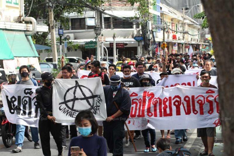 Demonstrators carry banners declaring,