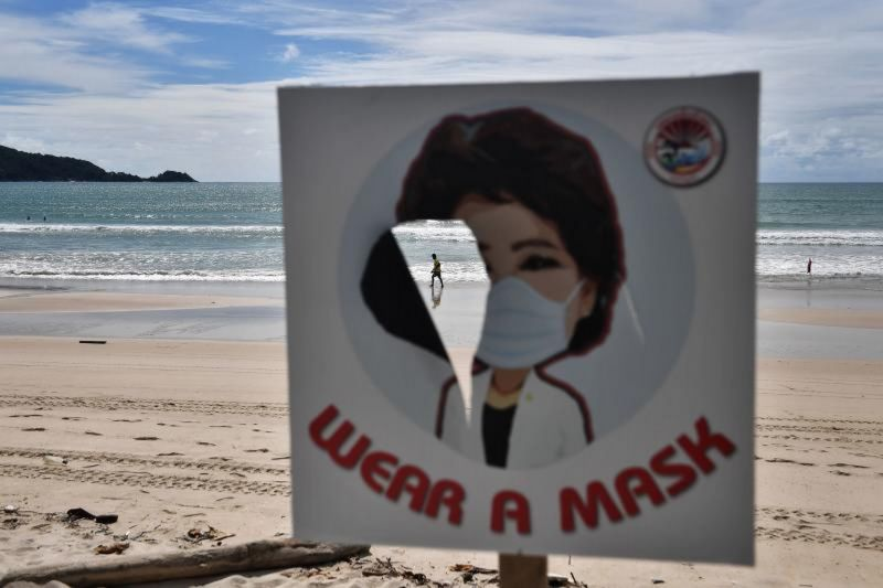 A man walks along the empty beach at Patong, Phuket, seen through a torn sign telling people to wear a mask, on Oct 1. Photo: Lillian Suwanrumpha / AFP