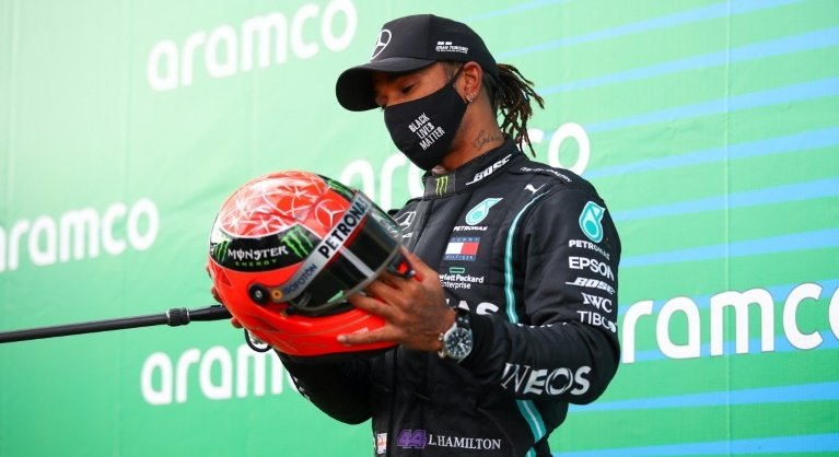 Hamilton, presented with one of Michael Schumacher's helmets at Nurburgring, seeks to claim record outright. Photo: AFP.