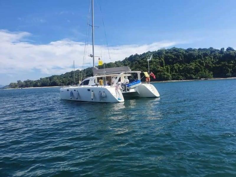 Health workers test new arrivals on yachts at the designated mooring area off Phuket's east coast. Photo: Eakkapop Thongtub