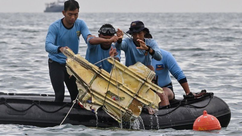 Navy divers hold wreckage from Sriwijaya Air flight SJY182 at sea near Lancang island on Jan 10. Photographer: Photo: AFP