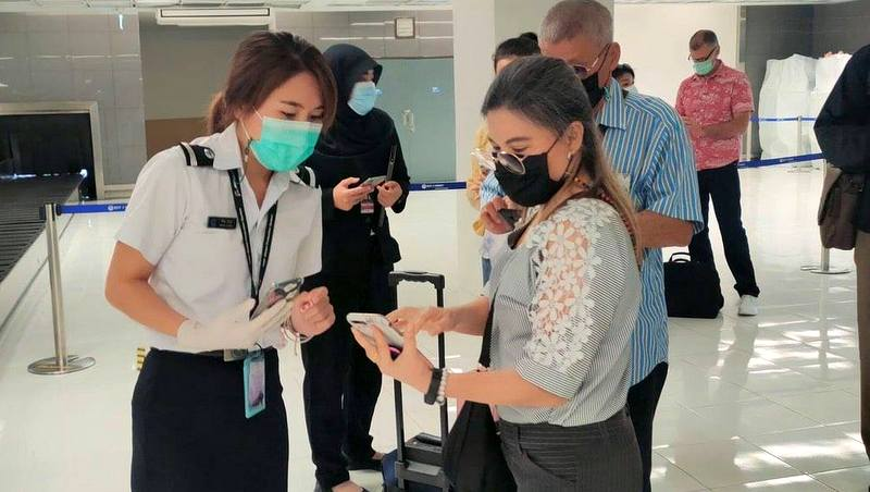 Staff at Phuket airport check arrivals to ensure they have the Mor Chana app installed. Photo: AoT Phuket