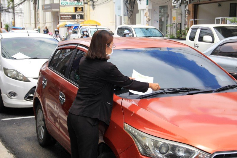 Phuket City Municipality staffers have been posting notices and informing local residents and shop owners of the parking ban. Photo: Phuket City Municipality