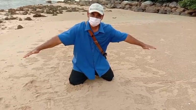 Mr Somchai indicates the size of the crocodile he saw. Photo: Eakkapop Thongtub